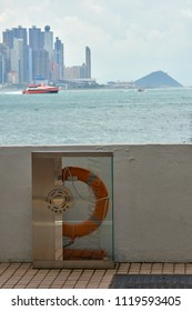 HONG KONG - September 5, 2017: Life buoy ring station at Victoria Harbour promenade with Hong Kong Island in background. Water safety concept.