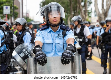 Hong Kong, Shatin 14th July 2019: Anti Extradition Bill Protest.  A uniformed police officer standing behind a large riot shield, wearing protective clothing.