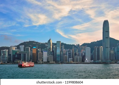 Hong Kong skyline cityscape downtown skyscrapers over Victoria Harbour in the evening with ferry boat on sunset. Hong Kong, China
