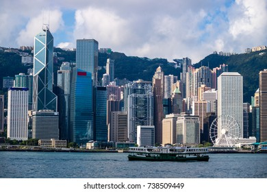 Hong Kong skyline cityscape, passenger ferry boat traffic on Victoria Harbor in morning dawn