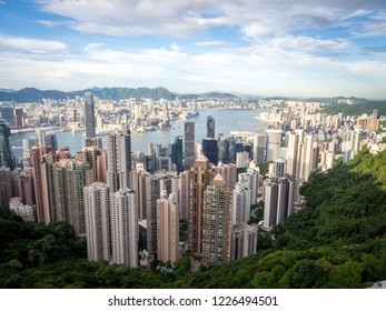 Hong Kong Skyline from the Famous Victoria Point at Daytime. Green forest and river surrounded by towering sky scrapers which is densly populated