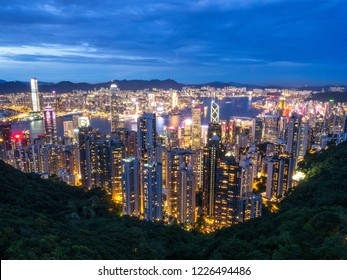 Hong Kong Skyline at Night from the Famous Victoria Point at Daytime. Green forest and river surrounded by towering sky scrapers which is densly populated. Deep blue sky and illuminated tall buildings