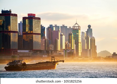 Hong Kong. Skyline of Hong Kong at sunrise. Beautiful skyscrapers with yellow sky in the morning. Typical industrial boat