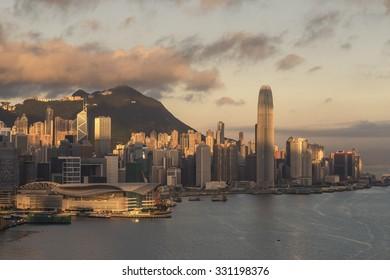 Hong Kong at Sunrise - The Rising Sun Lights Up Hong Kong Island with Victoria Peak and Wan Chai Ferry Terminal