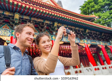 Hong Kong tourists couple visiting attraction Wong Tai Sin Temple taking selfie photo picture at Hong Kong landmark. Asia China travel sightseeing Taoist temple. Asian woman, Caucasian man.