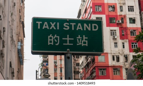 Hong Kong / Wan Chai / China / April 02 2019 Taxi stand sign in Chinese and English  close up with building background