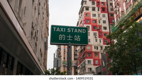 Hong Kong / Wan Chai / China / April 02 2019 Taxi stand sign in Chinese and English  wide shot with building background