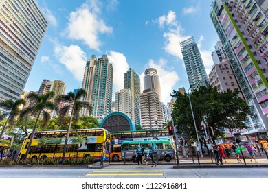 HONG KONG-AUGUST 13, 2017:  Unidentified people are seen around a traffic light, skyscrapers are seen on the background in city downtown. Hong Kong's population was about 7.34 million in 2016