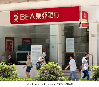 HONG KONG-AUGUST 14, 2017:  People walk pass a Bank of East Asia branch; The Bank of East Asia Limited, also known as BEA, was founded in 1918.