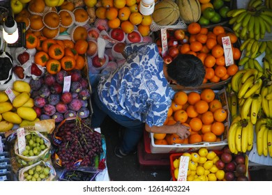 Hong Kong/China - October 26, 2017: Street vendor organizes fruit stand filled with colorful specimens on sale. Seen from above