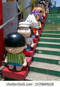 Hong Kong/China-May 28, 2018:  Seven cartoon characters lined up a set of stairs adjacent to Kowloon Park.