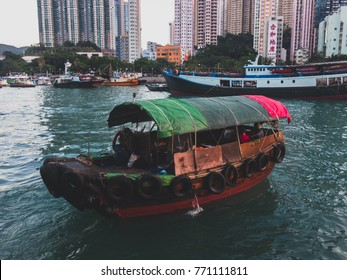 HONG KONG-DEC 8,2017:Traditional Sampans and Fishing Trawlers in Aberdeen Bay, Famous Floating Village many Residential Buildings on the Sides of Harbour.