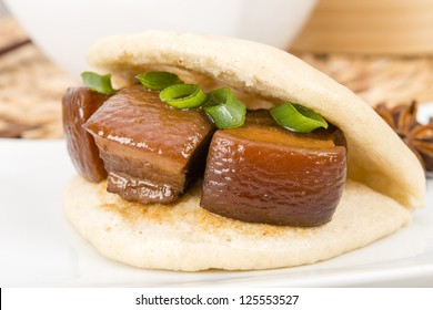 Hong Shao Rou (Red Cooked Pork) - Pork belly caramelized and braised in soy sauce with star anise, cinnamon and chilies inside a steamed bun (he ye bao).