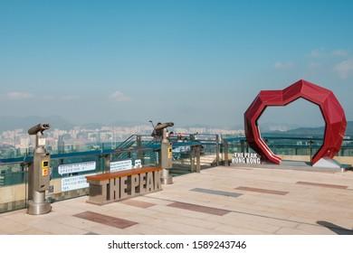 HongKong, China - November, 2019: People  enjoying the skyline view of HongKong from The Peak. It is the most popular attraction in Hong Kong