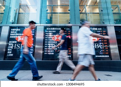 Hongkong, China - October 27, 2016: Pedestrians walk past a financial display board in front of a bank in Hong Kong, China.