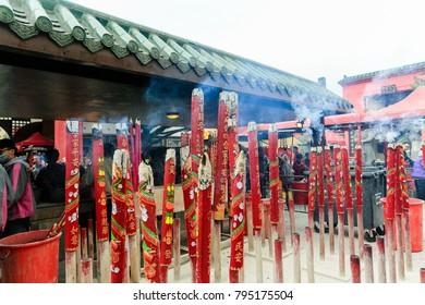 Hongkong/China February 08 2017 : Several red incenses  and smoke at the temple of Chinese faithful