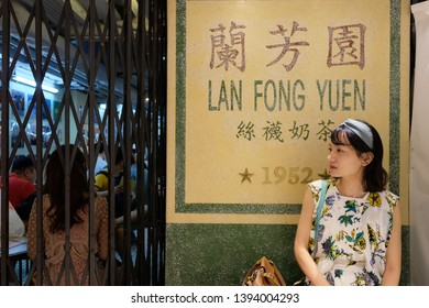 Hongkong/China- One young pretty girl sit in front of Lan Fong Yuen, a historic taste authentic tea restaurant in Hongkong. Famous for its toast and silk stocking milk tea