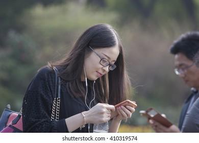 HONGMEI,CHANGZHOU,CHINA - MAY 16: Unidentified chinness girl listen song from telephone on May 03,2016 in Hongmei park,Changzhou,China.