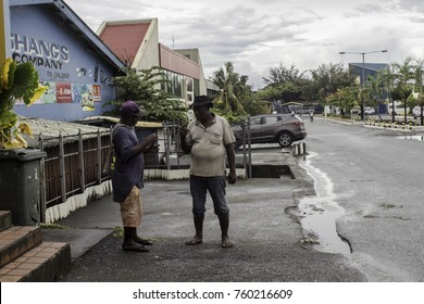 Honiara, Guadalcanal, Solomon Islands, Nov 2017, two men talking to each other on the sidewalk of the main Honiara street, Commonwealth street, on a quiet Sunday after the rain