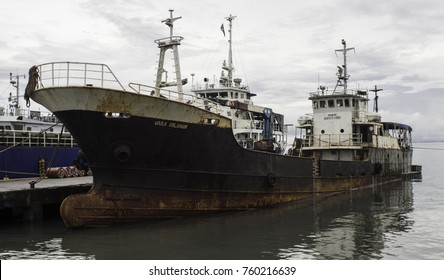 """Honiara, Guadalcanal, Solomon Islands, Point Cruz Ports, Nov 2017, the """"Vaka Solomon"""" (Solomon Canoe) is parked at the jetty with the """"Iron Bottom Sound"""" in the background with a lot of sunken WW2 shi"""