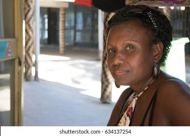 Honiara, Solomon Island - March 7th, 2017: Portrait of a melanesian woman sitting outside her souvenirs shop in Honiara.