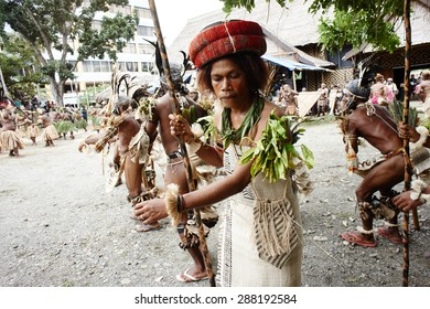"""Honiara, Solomon Islands, June 21, 2014, a traditional dancing group from Temotu province performs at the museum area. The woman carries a traditional roll of 'feathermoney"""" (brideprice) on her head"""