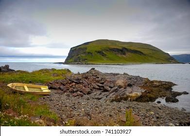 Honningsvag, Mageroya Island - Nordkapp, Norway. View across sea to Nordvagholmen island.  Summer scene, green slopes, rocky coastline and yellow boat