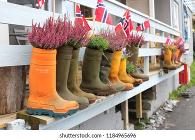 Honningsvag, Norway, August 26th 2018: Plants and Norwegian flags in boots, Honningsvag