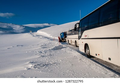 HONNINGSVAG, NORWAY -MAR 2015 : two tourist coaches are waiting to leave towards the North Cape, preceded, for safety, by a big snow truck in Honningsvag, around March 2015.