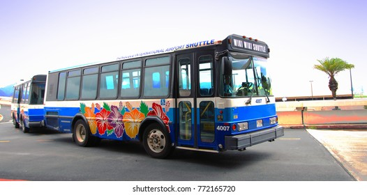 HONOLULU, HAWAII—AUGUST 2015: A colorful blue and white Wiki Wiki shuttle waits for passengers outside the arrival area of the Daniel K. Inouye International Airport or Honolulu International Airport.