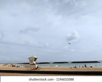 Honolulu - April 21, 2018:  People play at Beach on Magic Island with Lifeguard Tower in Ala Moana Beach Park on the island of Oahu, Hawaii with helicopter in the air on a beautiful day.
