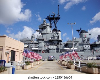 Honolulu - April 26, 2010: Row of USA Flags leading to the USS Missouri with radar and satellite towers at midship visible on Oahu, Hawaii.
