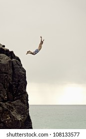 "HONOLULU - AUG 2011: An unidentified man jumps off a 30 foot high rock, known as ""Da Big Rock"", into Waimea Bay below on Aug 20, 2011 in Honolulu."