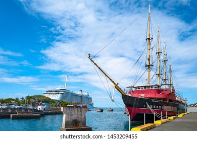 Honolulu, Awaii - May 3, 2019: An ancient sail boat with a cruise ship in the background in the Honolulu harbor
