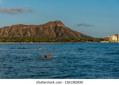 Honolulu, Hawaii - April 1, 2019: Surfer at sunset paddling out to catch a wave off Waikiki, Hawaii. Diamond Head volcano is in the background.