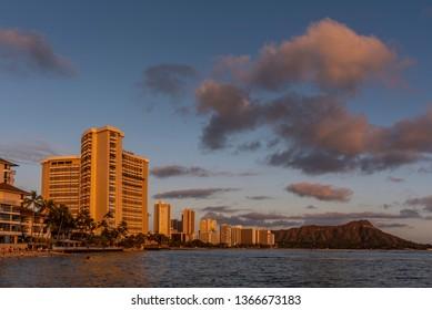 Honolulu, Hawaii - April 1, 2019: View of famous Waikiki Beach and Diamon Head volcano at sunset. Tourists visible on beach.