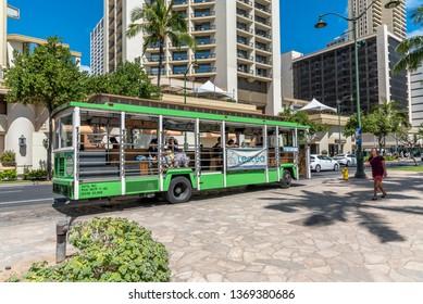 Honolulu, Hawaii - April 1, 2019:  The Waikiki Trolley bus on Kalakaua Avenue in Waikiki.  Many tourist buses drive tourists around beautiful Honolulu and Oahu islands.