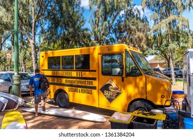 Honolulu, Hawaii - April 4, 2019:  Surf School bus parked on the shore along beautiful Waikiki Beach in Honolulu