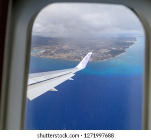 Honolulu, Hawaii - Dec 22, 2018 : Wing of Hawaiian Airlines plane flying in the air above Honolulu