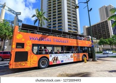 Honolulu, Hawaii - Dec 23, 2018 : Waikiki Trolley bus on Kalakaua avenue, Waikiki beach