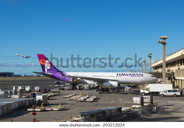HONOLULU, HAWAII - JUNE 24 2014: Hawaiian Airlines planes on the ground and in the air at Honolulu International Airport in Hawaii
