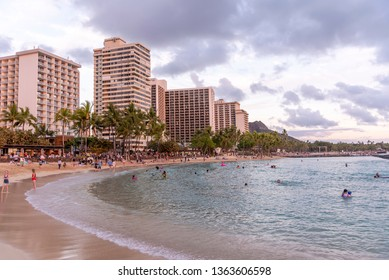 Honolulu, Hawaii - March 31, 2019: Views along Waikiki Beach during a beautiful sunset.  Waikiki is famous for its sunsets and many tourists line the beaches for sunset photos and selfies.