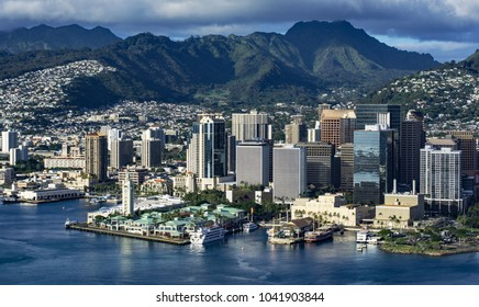 HONOLULU, HAWAII - MARCH 7, 2018: Aerial view of the downtown Honolulu skyline with the Koolau Mountains in the background. On the left is Aloha Tower.