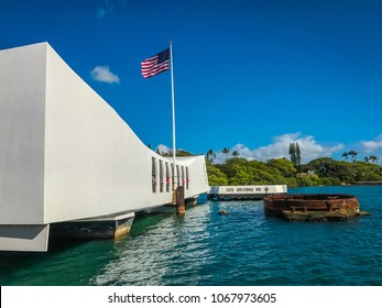 Honolulu, Hawaii - May 12, 2017: USS Arizona Memorial beneath a waving US flag and a clear blue sky. Includes both the memorial structure and the ship's forward smokestack.