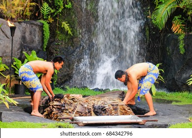 Honolulu, Hawaii - May 27, 2016: Two young Hawaiian men at the Polynesian Cultural Center uplift a pig cooked in the traditional style Kalua utilizing an Imu (under ground oven)