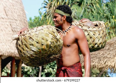 Honolulu, Hawaii - May 27, 2016:A Samoan man carrying coconuts in a traditionally woven pair of baskets in the village of Samoa at the Polynesian Cultural Center.