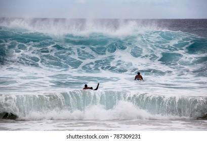 Honolulu, Hawaii / USA - 01 04 2018: Surfers trying to catch waves at Hawaiian beach.