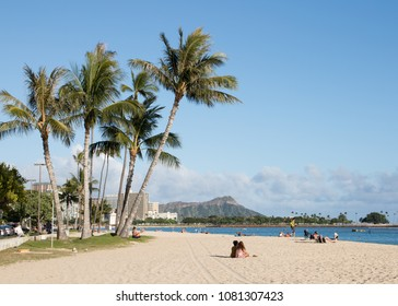 Honolulu, Hawaii, USA, 25. April, 2018: Palm trees and beach activity on a sunny day at Ala Moana Beach Park with Diamond Head mountain in the background