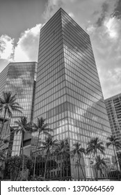 Honolulu, Hawaii, USA.  Apr. 16, 2019.  Financial District new glass skyscrapers with tropical palm trees and sunny skies.