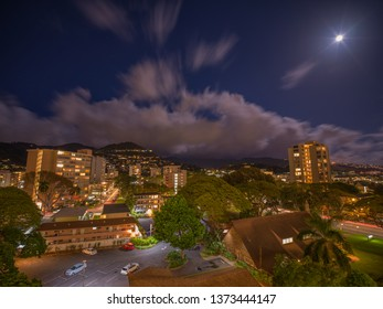 Honolulu, Hawaii, USA.  Apr. 18, 2019.  Night time lapse view of fast moving clouds and a rising full moon above Manoa Valley.